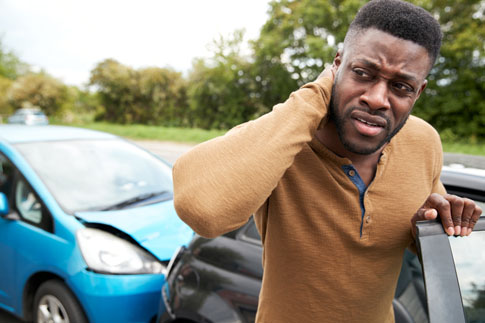 Man holding neck after car accident